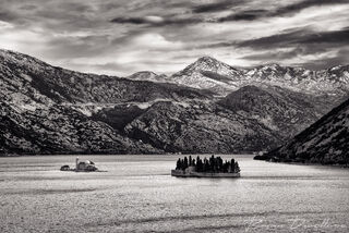 Islets in the Bay of Kotor against mountain backdrop in Montenegro in black and white.