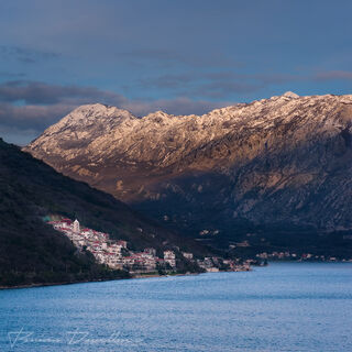 View of Kotor Bay with sunlight mountains in the background near Kotor, Montenegro.