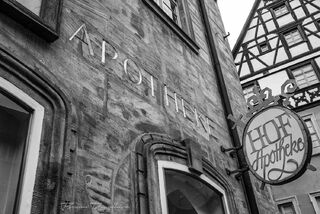 Facade of the oldest pharmacy in Bavaria, Germany from below in black and white.