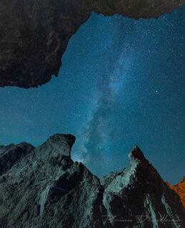 A starry sky viewed from below between seastacks in Bandon, Oregon.