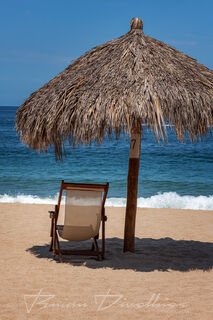 Solitary beach chair and palm front umbrella on the sand in front of the ocean in Jalisco, Mexico.