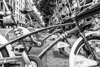 Line of bikes for rent on the street in Barcelona, Spain in black and white.