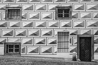 Patterned facade of armory building on the grounds of the Prague Castle complex in Prague, Czech Republic, in black and white.