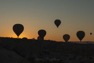 Hot air balloons viewed from the air over Cappadocia, Turkey at sunrise.
