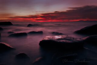Purple-toned sunset over rocks in the ocean in Puerto Vallarta, Mexico.