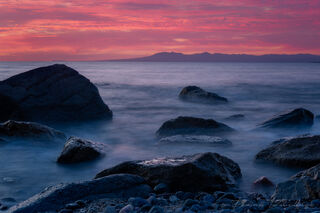 Sunset over a rocky beach in Puerto Vallarta, Mexico.