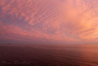 Empty pink sky, sea, and clouds in waters near Helsinki, Finland.
