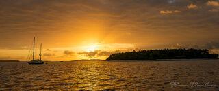 Dawn breaks behind an island and sailboat in Vava'u, Tonga.
