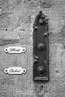 Doorbell with name plates in Old Town of Bavaria, Germany in black and white.