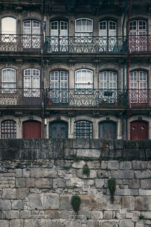Wall of balconies with colorful windows and doors along Cais da Estiva in Porto, Portugal.