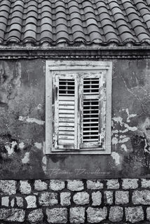Closed window shutters on the Old Town wall walk in Dubrovnik, Croatia, in black and white.