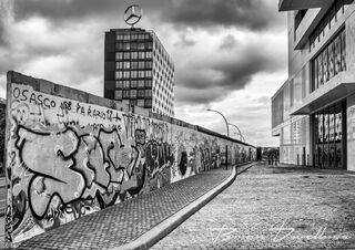 Stretch of Berlin Wall covered in graffiti with city buildings on either side in black and white.