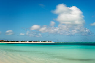 Layers of turquoise ocean and beach below clouds in a blue sky in Turks and Caicos.