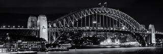 Black and white panorama of Sydney Harbour Bridge at night.