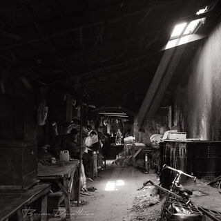Light spills onto subterranean laundry workers at Dhobi Ghat in Mumbai, India in black and white.