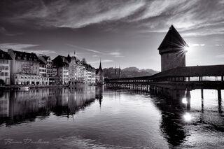 Sun behind the 14th Century Chapel Bridge (Kapellbrücke) spanning the Reuss River in Lucerne, Switzerland in black and white.