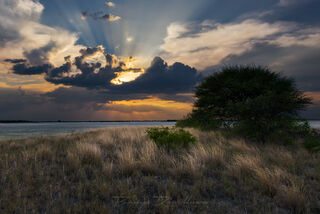 A colorful sunset with light rays streaming through the clouds over Kudiakama Pan, Nxai Pan National Park, Botswana