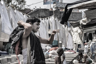 Man carrying clothes beneath hanging garments at Dhobi Ghat in Mumbai, India in black and white.