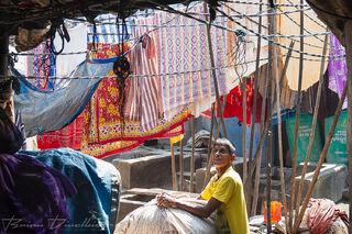 Woman outdoors among colorful hanging garments at Dhobi Ghat in Mumbai, India.