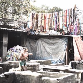 Man walks between open air laundry tubs at Dhobi Ghat in Mumbai, India.