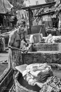 Man at open air laundry tub at Dhobi Ghat in Mumbai, India in black and white.