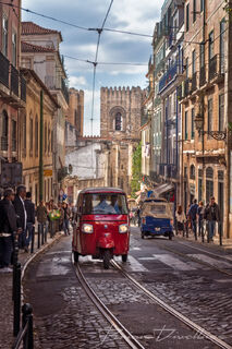 Red tuk-tuk drives down road leading to the Lisbon Cathedral in Lisbon, Portugal.