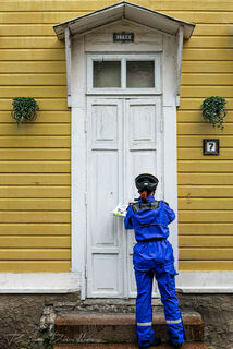 Mail carrier in blue holds mail and faces white door of yellow house in Porvoo, Finland.