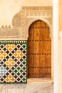 Wooden door surrounded by Moorish carvings and mosaics in La Alhambra in Granada, Spain.