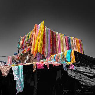 Colorful hanging saris against black and white background at Dhobi Ghat in Mumbai, India.