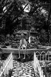 A decorated skeleton sits in front of a stone monument over a mosaic path in Puerto Vallarta, Mexico in black and white.