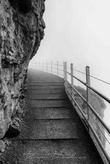 Stairs on the path to Aescher Wildkirchli receding into the fog on Ebenalp, Switzerland in black and white.