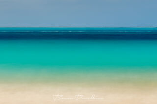 Layers of turquoise ocean and beach below a clear sky in Turks and Caicos.