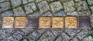 Jewish stumbling blocks (Stolpersteine) in cobblestone street of Baden-Württemberg, Germany.