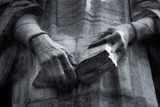Close-up of stone hands of Calvin holding a bible in the Old City of Geneve, Switzerland.