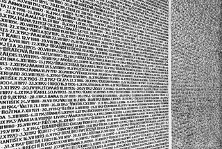 A wall in the Jewish Museum of Prague depicting the names of Jewish citizens from Prague deported to concentration camps during World War II in black and white.