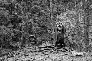 Carved wooden faces along the hike down from Mt. Floyen in Bergen, Norway, in black and white.