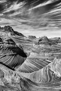 The Wave and Vermilion Cliffs National Monument below a cloud-streaked sky taken from the Wave Trail in black and white.