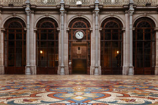 Clock among arches above floor mosaic in the Stock Exchange Palace of Porto, Portugal.