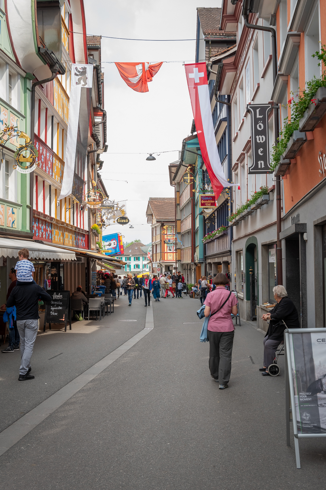 Colorful shopfronts line a street in Appenzell, Switzerland.