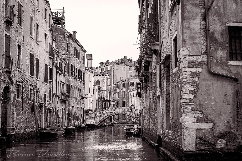 A classic scene of Venice -- canals, boats, bridges, and umbrella toting Venetians.