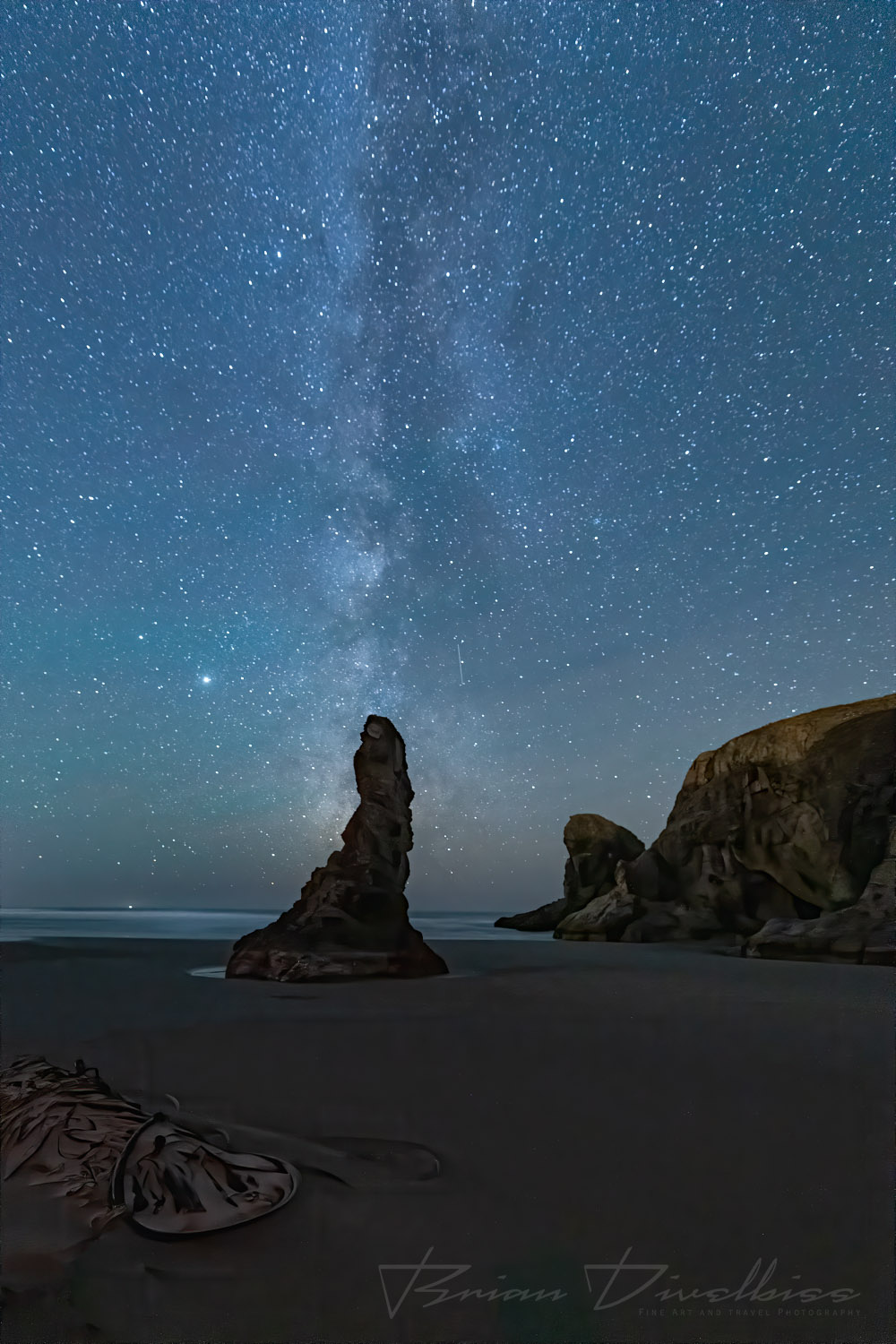 A seastack on the beach points to the starry sky above in Bandon, Oregon.