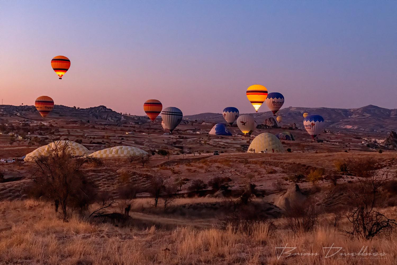 Hot air balloons viewed from the air over Cappadocia, Turkey at dawn.