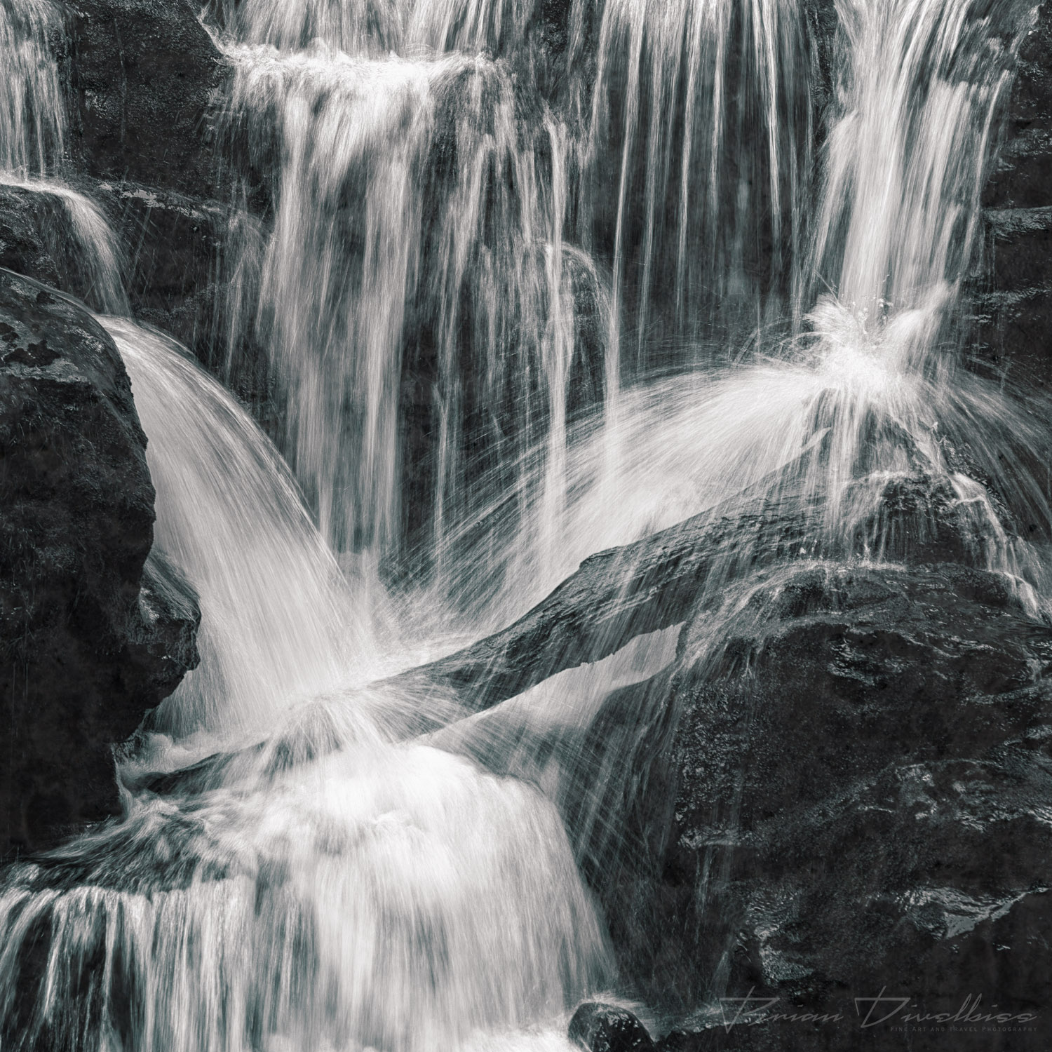 Water falls and bounces over rocks in Oregon in black and white.