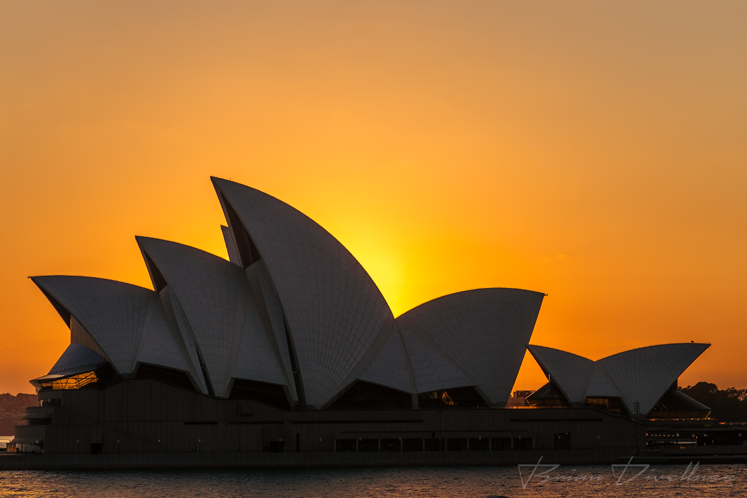 Sun rising behind Sydney Opera House viewed from Dawes Point.