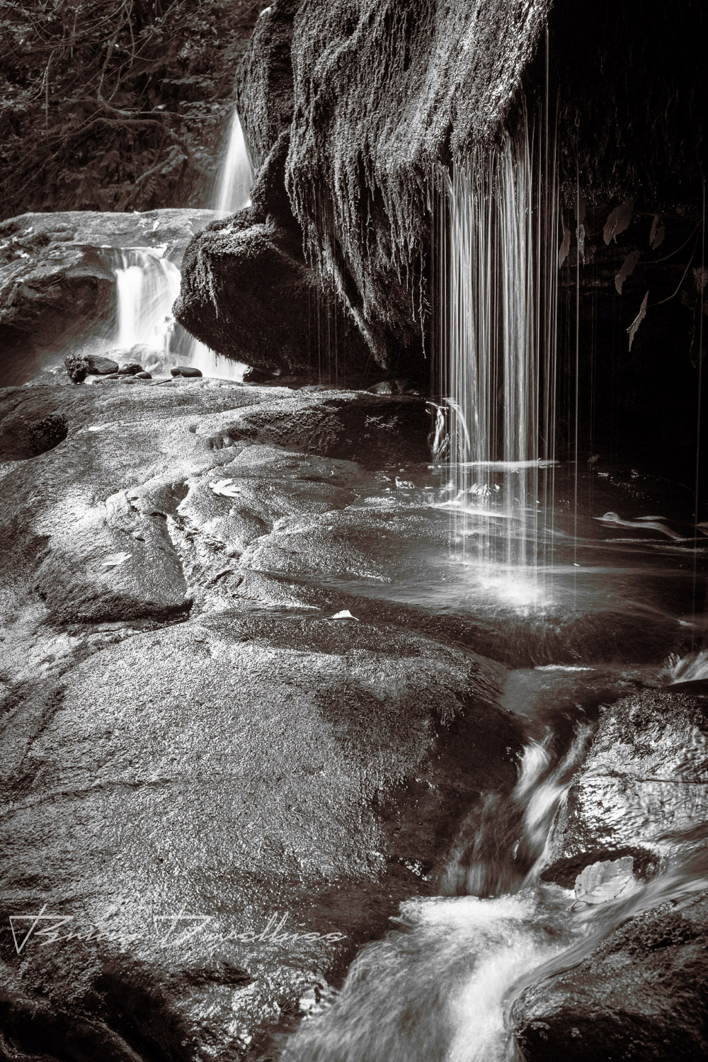 Thin waterfalls over dark rock viewed from the side in Oregon in black and white.