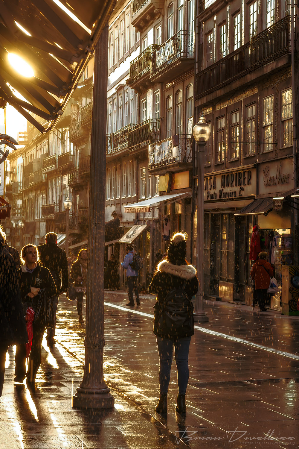 Pedestrians standing in golden light of a rainy day in Porto, Portugal.