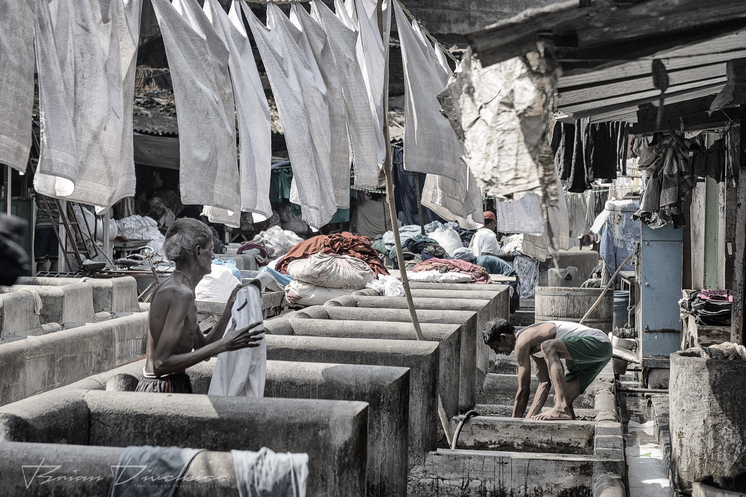 Row of outdoor laundry tubs beneath hanging clothes at Dhobi Ghat in Mumbai, India in black and white.