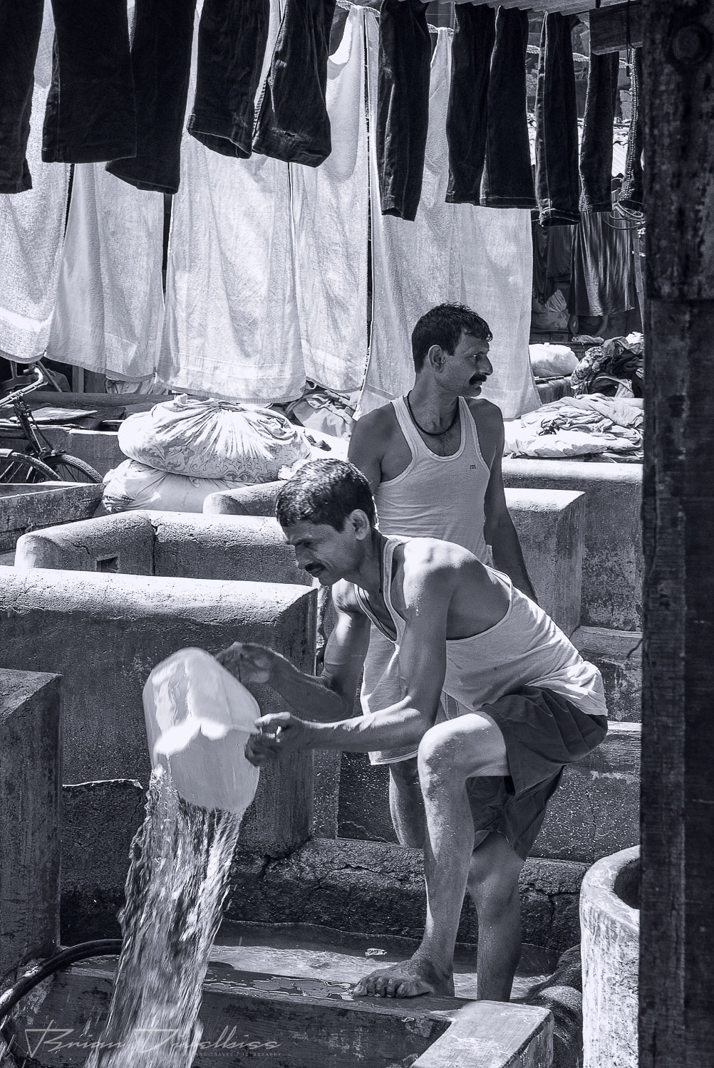 Man pulls clothes from an outdoor laundry tub at Dhobi Ghat in Mumbai, India in black and white.