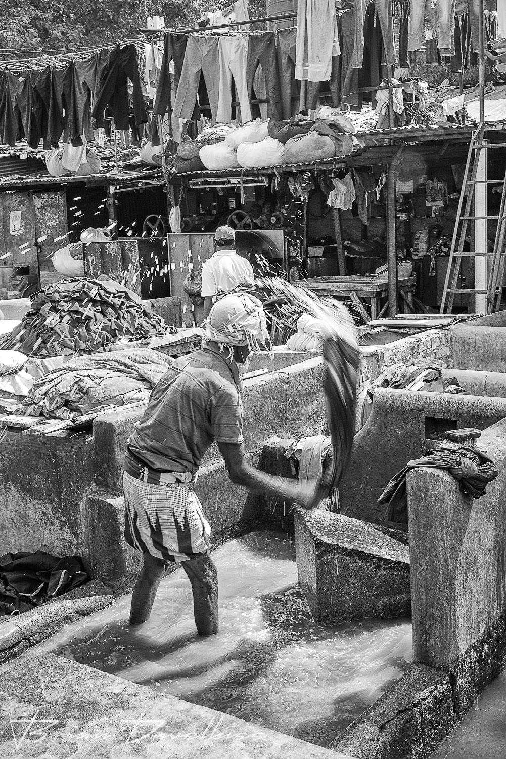 People doing laundry outdoors under hanging garments at Dhobi Ghat in Mumbai, India in black and white.
