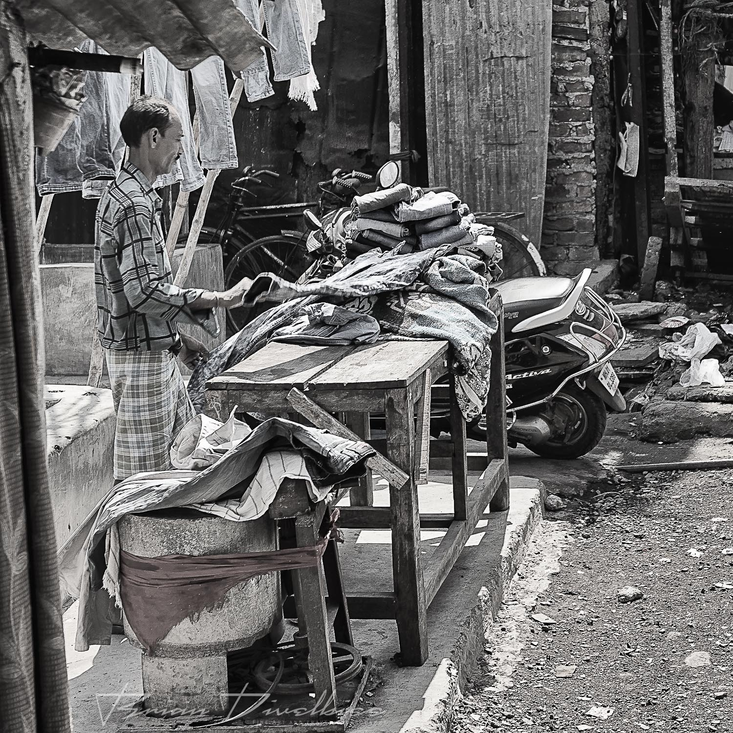 Textile worker with table of fabric at Dhobi Ghat in Mumbai, India in black and white.